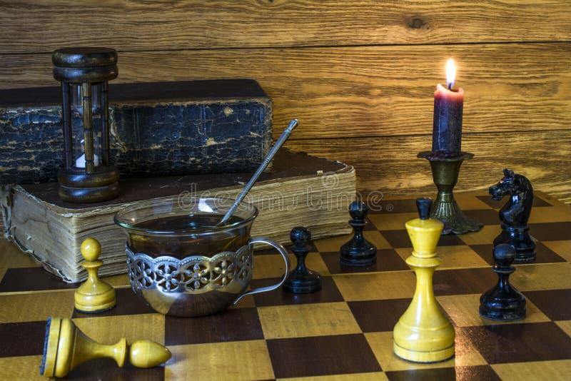 Κλεψύδρα, κομμάτια σκακιού, ένα φλυτζάνι του τσαγιού, μια καίγοντας στάση κεριών σε μια σκακιέρα στοκ εικόνα