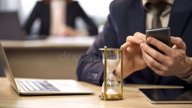 Κλεψύδρα που μετρά το χρόνο, επιχειρηματίας που χρησιμοποιεί το κινητό τηλέφωνο, αναβλητικότητα στοκ εικόνα