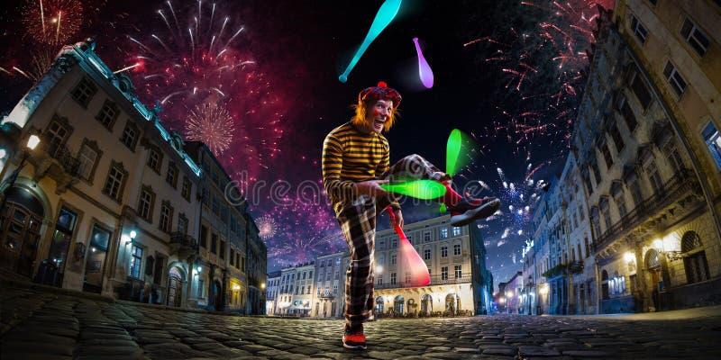 Κλόουν μορίων απόδοσης τσίρκων οδών νύχτας, ζογκλέρ Υπόβαθρο πόλεων φεστιβάλ πυροτεχνήματα και ατμόσφαιρα εορτασμού Ευρύ engle στοκ εικόνες