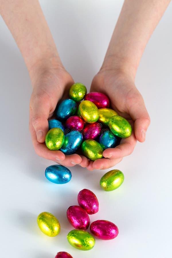 Κοίλα χέρια που κρατούν τα μικρά αυγά Πάσχας ανατρέποντας επάνω στην επιφάνεια στοκ φωτογραφία με δικαίωμα ελεύθερης χρήσης