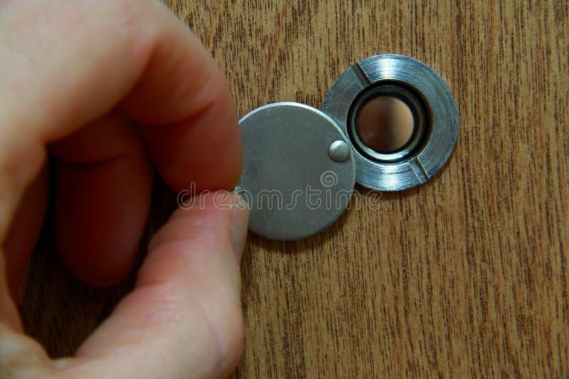 Κοίταγμα μέσω του ματάκι πόρτας στοκ φωτογραφία