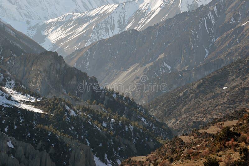 Κοίταγμα πέρα από τον τίτλο κοιλάδων προς τη λίμνη Tilicho και τα απότομα πλαισιωμένα βουνά των Ιμαλαίων Στο κύκλωμα Annapurna ν στοκ φωτογραφία