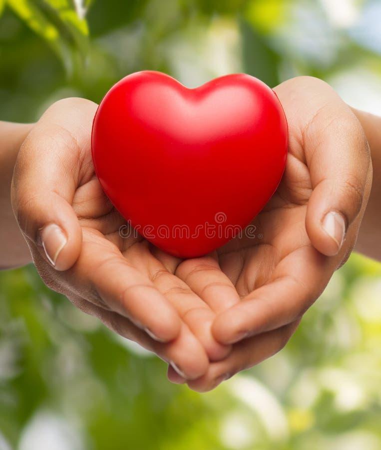 Κοίλα χέρια γυναίκας που παρουσιάζουν κόκκινη καρδιά στοκ φωτογραφία