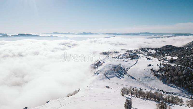 Κοιλάδα πάνω από το βουνό που καλύπτεται με το χιόνι πέρα από τα σύννεφα μια ηλιόλουστη ημέρα που φωτογραφίζεται από τον αέρα στοκ εικόνα με δικαίωμα ελεύθερης χρήσης