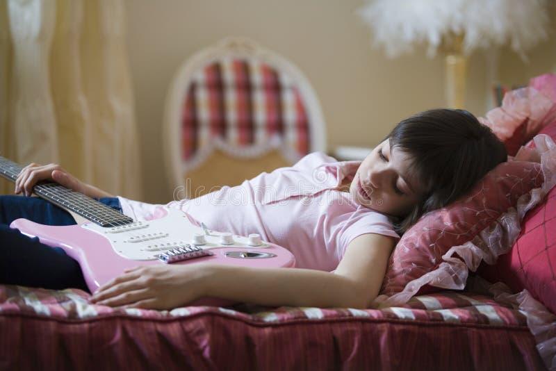 Κοιμισμένη ηλεκτρική κιθάρα εκμετάλλευσης κοριτσιών στο κρεβάτι στοκ φωτογραφίες