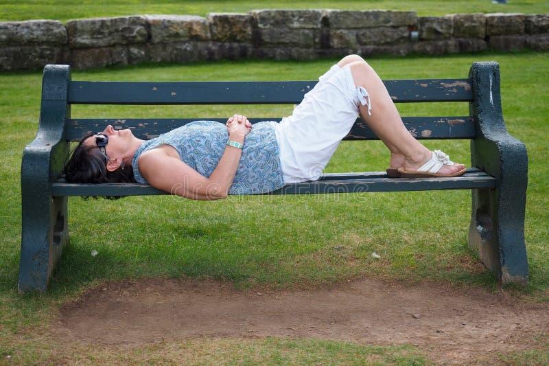 Κοιμισμένος στον πάγκο πάρκων στοκ φωτογραφία