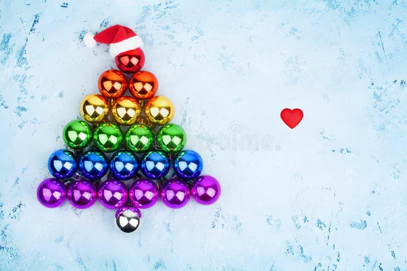 Κοινοτικά χρώματα σημαιών ουράνιων τόξων σφαιρών LGBTQ διακοσμήσεων χριστουγεννιάτικων δέντρων, καπέλο Άγιου Βασίλη, κόκκινη καρδ στοκ φωτογραφία