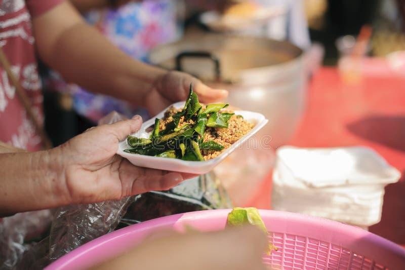 Κοινωνικά προβλήματα της ένδειας που ενισχύονται με τη σίτιση: Εθελοντής για να ταΐσει τον πεινασμένο στην κοινωνία: Η έννοια να  στοκ φωτογραφίες