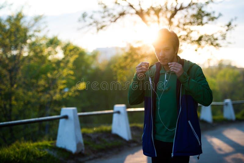 Κοινός νεαρός άνδρας που περπατά στην πόλη που ακούει στη μουσική με τα ακουστικά -αυτιών στο ηλιοβασίλεμα Θέμα μουσικής στο σχέδ στοκ φωτογραφία με δικαίωμα ελεύθερης χρήσης
