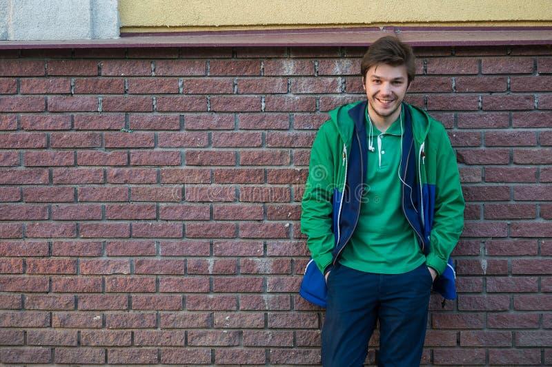 Κοινός νεαρός άνδρας που φορά το πράσινα σακάκι και τα τζιν μπλουζών ενάντια σε έναν τούβλινο τοίχο που κοιτάζει στη κάμερα στοκ φωτογραφίες με δικαίωμα ελεύθερης χρήσης