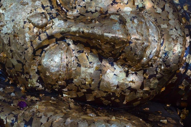 Κοισμένος μαύρο κεφάλι του Βούδα που καλύπτεται με τα χρυσά φύλλα στοκ φωτογραφία με δικαίωμα ελεύθερης χρήσης