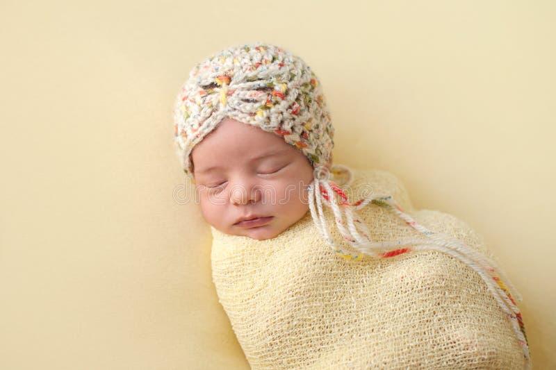Κοισμένος νεογέννητο κοριτσάκι Swaddled σε κίτρινο στοκ φωτογραφία