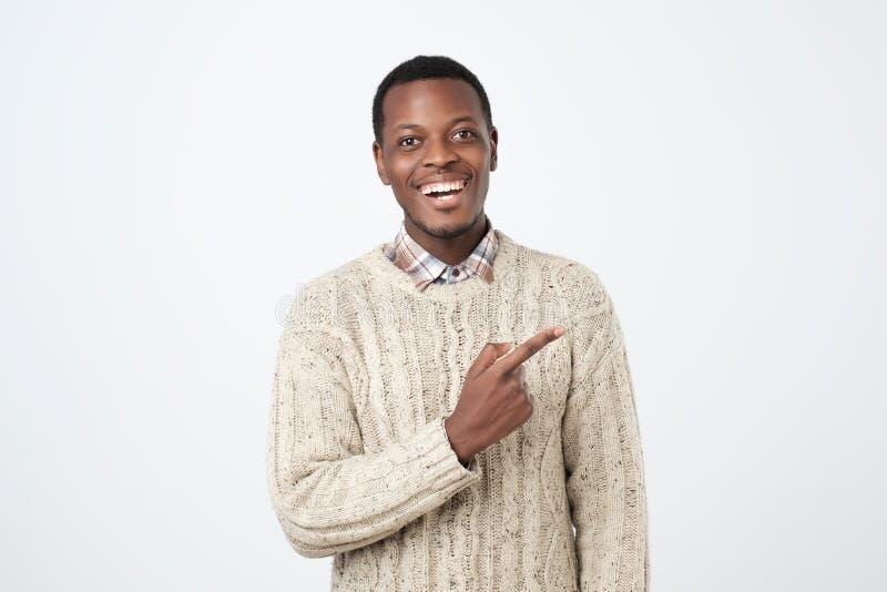 Κοιτάξτε εκεί Ευτυχές νέο όμορφο αφρικανικό άτομο που δείχνει μακριά και που χαμογελά στοκ φωτογραφία