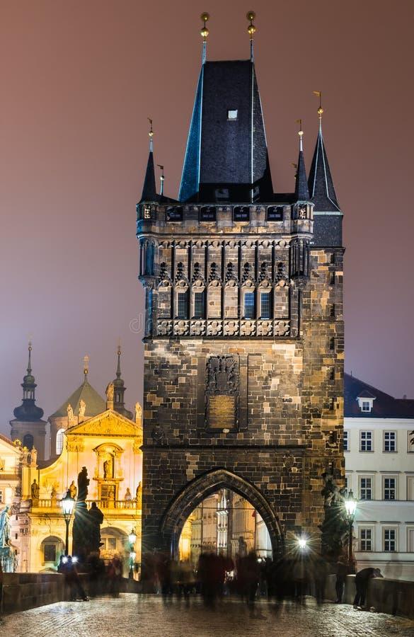 Κοιτάξτε επίμονα τον πύργο Mesto από τη γέφυρα του Charles τη νύχτα, Πράγα. στοκ φωτογραφία