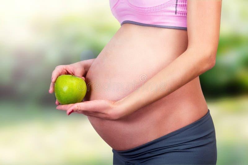 Κοιλία των εγκύων γυναικών και του πράσινου μήλου στοκ φωτογραφίες