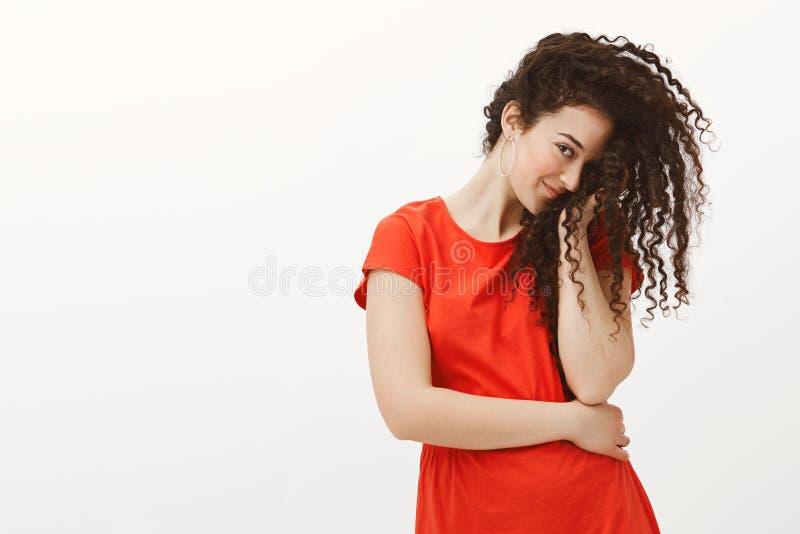 Κοκκινίζοντας flirty φίλη στο κόκκινο φόρεμα, καλύπτοντας το μισό από το πρόσωπο με τη σγουρή τρίχα και κοιτάζοντας επίμονα με έν στοκ φωτογραφίες με δικαίωμα ελεύθερης χρήσης