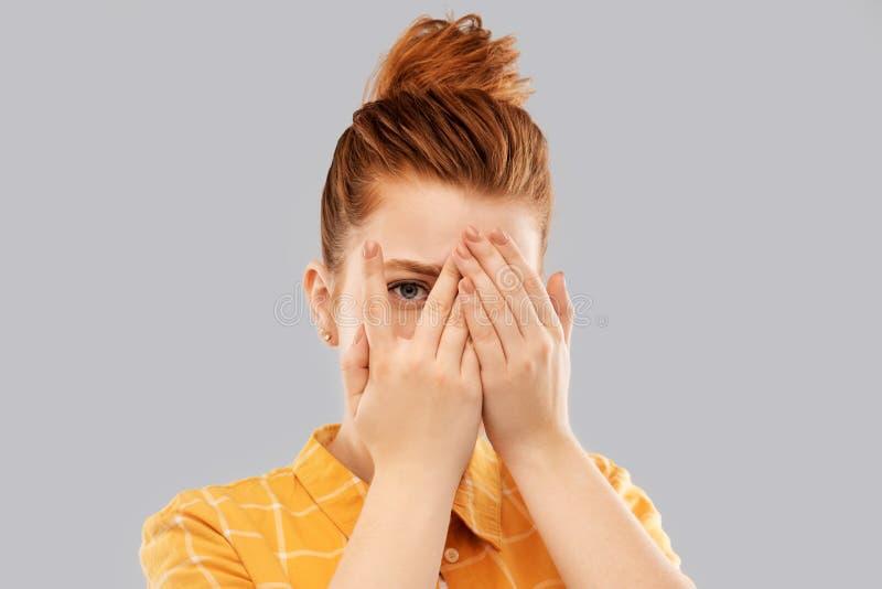 Κοκκινομάλλες έφηβη που κοιτάζει μέσω των δάχτυλων στοκ φωτογραφία