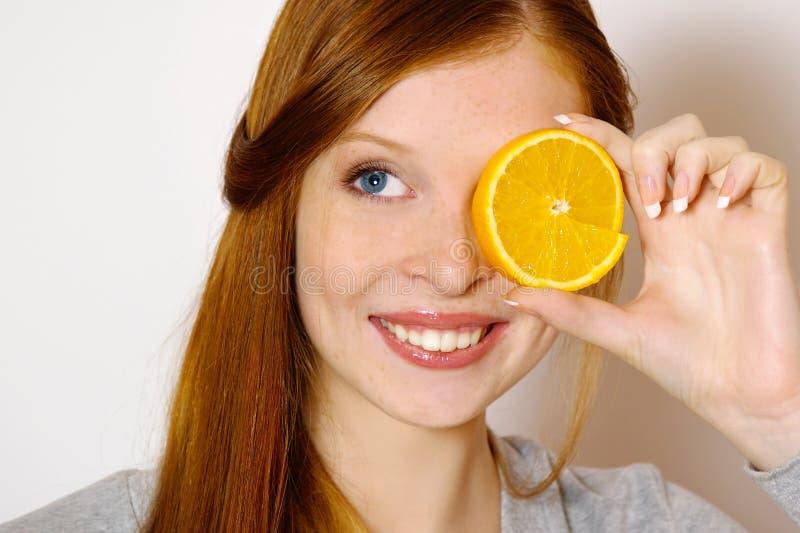 Κοκκινομάλλες κορίτσι με το πορτοκάλι στοκ εικόνες με δικαίωμα ελεύθερης χρήσης