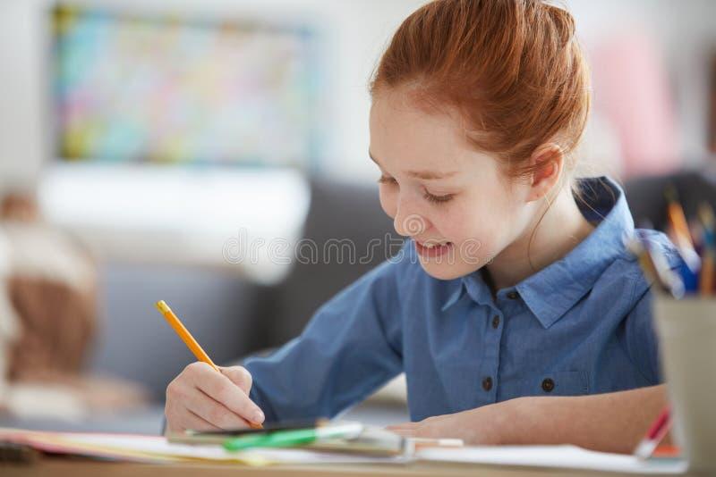Κοκκινομάλλες κορίτσι που κάνει την εργασία στοκ φωτογραφία
