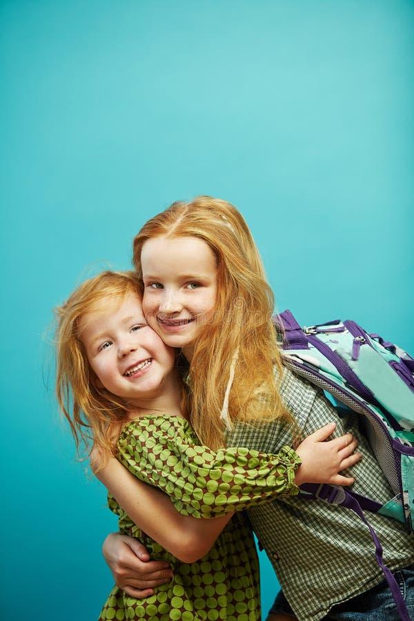 Κοκκινομάλλες χαριτωμένο αγκάλιασμα αδελφών παιδιών δύο που απομονώνεται στο μπλε υπόβαθρο στοκ εικόνες με δικαίωμα ελεύθερης χρήσης