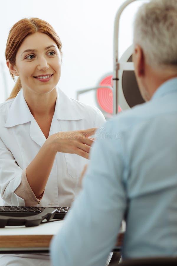 Κοκκινομάλλης γιατρός ματιών που ελέγχει τη θέα ματιών του συνταξιούχου ατόμου στοκ εικόνα με δικαίωμα ελεύθερης χρήσης
