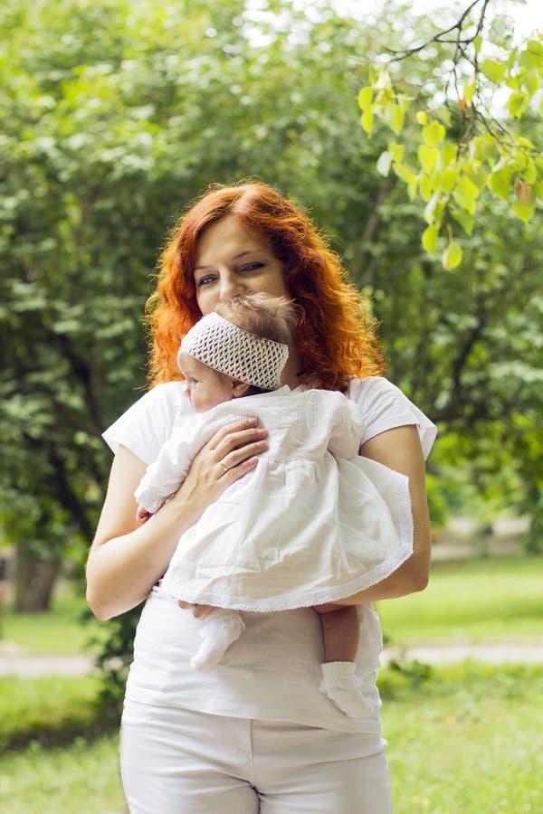Κοκκινομάλλης γυναίκα με λίγο μωρό στο πάρκο Μικρό κορίτσι στο άσπρο φόρεμα, τις κάλτσες και πλεκτό headband στοκ φωτογραφίες με δικαίωμα ελεύθερης χρήσης