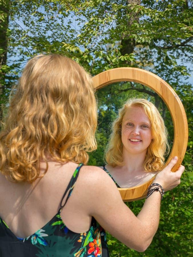 Κοκκινομάλλης γυναίκα που εξετάζει την αντανάκλαση καθρεφτών της στοκ εικόνες με δικαίωμα ελεύθερης χρήσης
