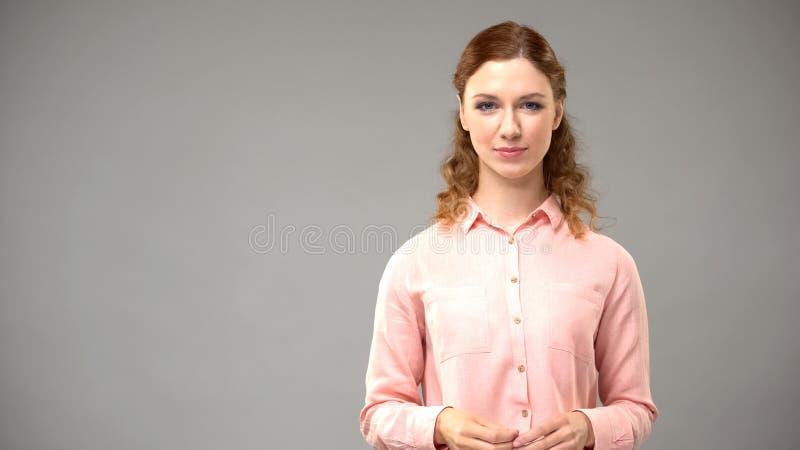 Κοκκινομάλλης γυναίκα στη ρόδινη μπλούζα που φαίνεται κεκλεισμένων των θυρών στο γκρίζο υπόβαθρο, πρότυπο στοκ φωτογραφίες