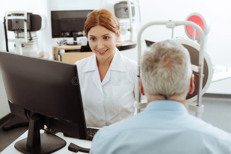 Κοκκινομάλλης νέος αλλά επαγγελματικός γιατρός ματιών που εργάζεται σκληρά στοκ φωτογραφία