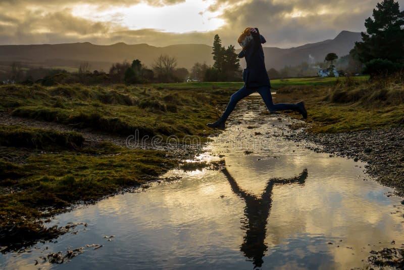Κοκκινομάλλη άλματα κοριτσιών πέρα από ένα ρεύμα στο νησί Arran, Scot στοκ εικόνες