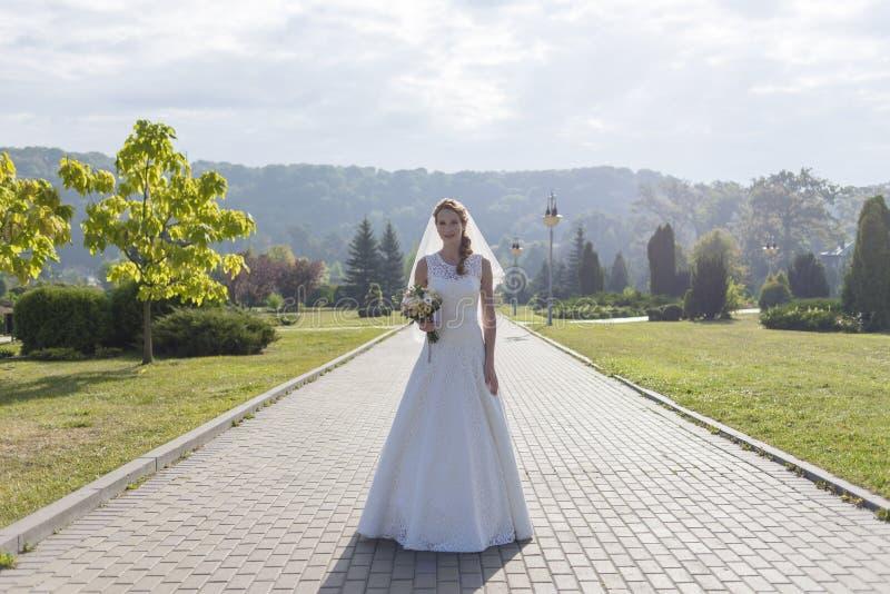 Κοκκινομάλλες κορίτσι στο άσπρο μακρύ φόρεμα κάτω από το ανοιχτό ουρανό στοκ εικόνες με δικαίωμα ελεύθερης χρήσης