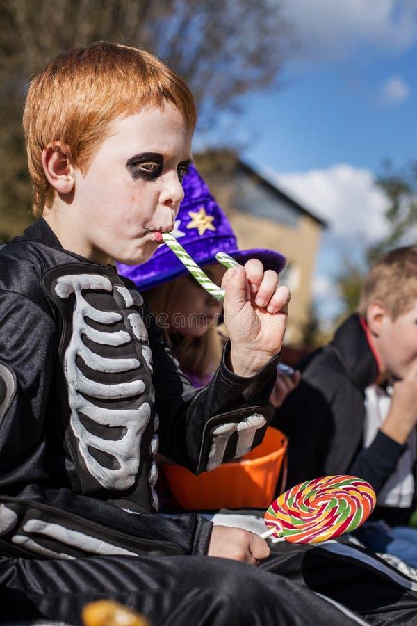 Κοκκινομάλλες παιδί με το κοστούμι σκελετών που τρώει τη ζωηρόχρωμη καραμέλα αποκριές στοκ φωτογραφίες με δικαίωμα ελεύθερης χρήσης