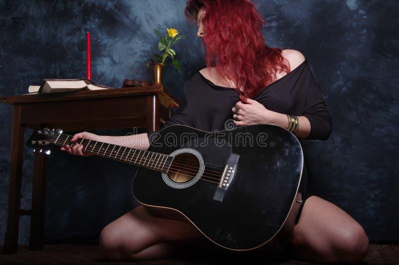 Κοκκινομάλλης γυναίκα και η μαύρη ακουστική κιθάρα στοκ φωτογραφία με δικαίωμα ελεύθερης χρήσης