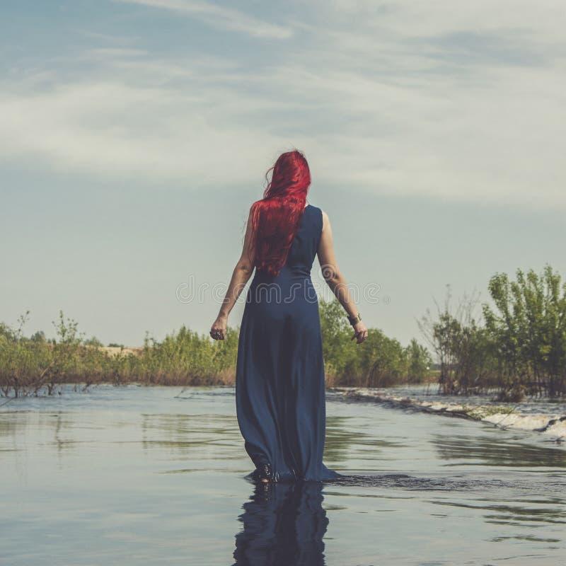 Κοκκινομάλλης γυναίκα που περπατά στον ποταμό στοκ φωτογραφία με δικαίωμα ελεύθερης χρήσης