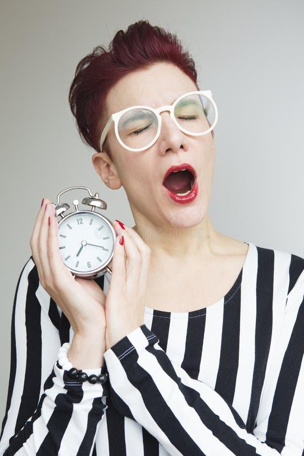Κοκκινομάλλης γυναίκα που χασμουριέται και που κρατά το ξυπνητήρι στοκ φωτογραφία