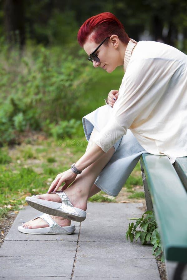 Κοκκινομάλλης συνεδρίαση γυναικών στον πάγκο και ρύθμιση του παπουτσιού της στοκ φωτογραφία με δικαίωμα ελεύθερης χρήσης