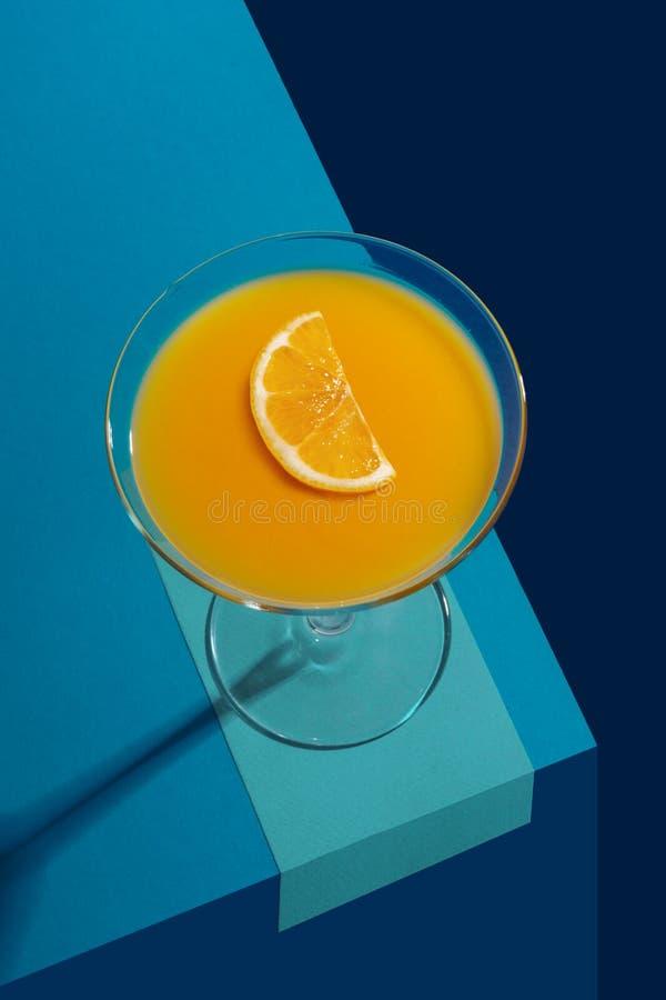 Κοκτέιλ με το λεμόνι σε μια κούπα γυαλιού σε ένα μπλε αφηρημένο υπόβαθρο E στοκ φωτογραφία