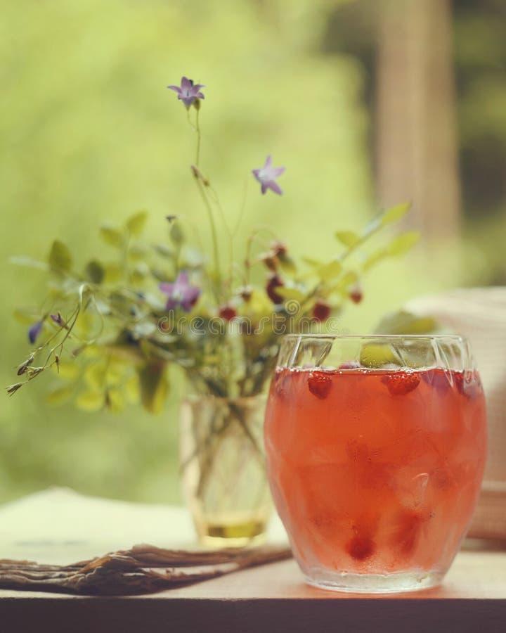 Κοκτέιλ φραουλών σε ένα φλυτζάνι γυαλιού τη θερινή ημέρα βεραντών windowsill με μια ανθοδέσμη της διάθεσης λουλουδιών υπαίθρια στοκ φωτογραφία