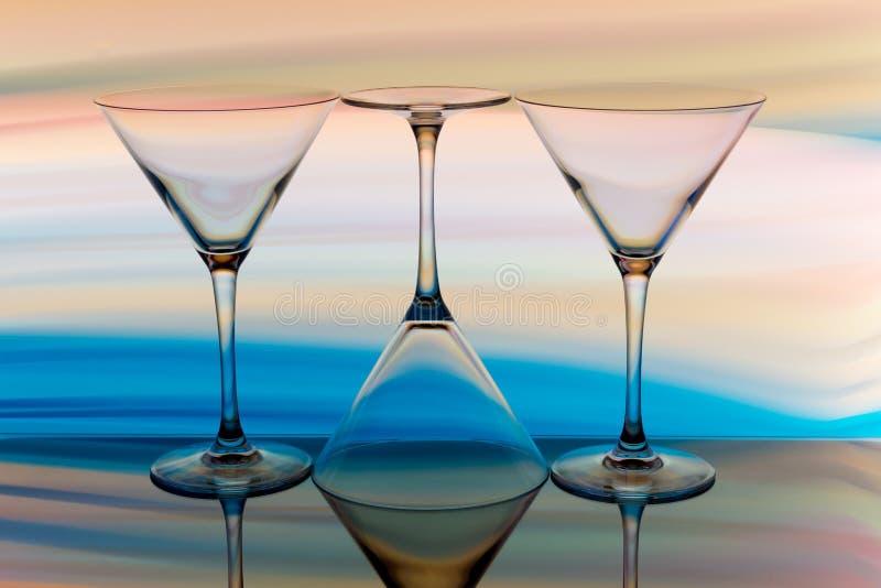 Κοκτέιλ/martini γυαλί με ένα ουράνιο τόξο του χρώματος πίσω στοκ εικόνα