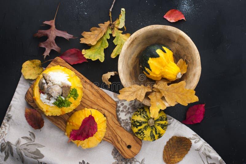 Κολοκύθα που ψήνεται με το κρέας ρύζι μανιταριών Εύγευστο γεύμα φθινοπώρου Ντεκόρ των φύλλων σε ένα μαύρο υπόβαθρο Ελεύθερου χώρο στοκ φωτογραφίες