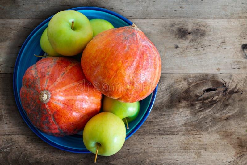 Κολοκύθες και μήλα στο κεραμικό κύπελλο στον αγροτικό ξύλινο πίνακα κουζινών στοκ εικόνα με δικαίωμα ελεύθερης χρήσης