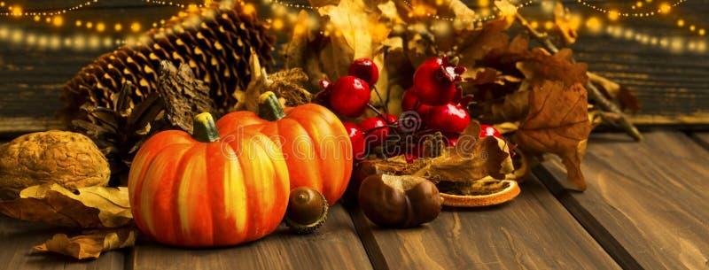 Κολοκύθες φθινοπώρου με τα εορταστικά φω'τα και διακοσμήσεις στο ξύλινο BA στοκ εικόνες