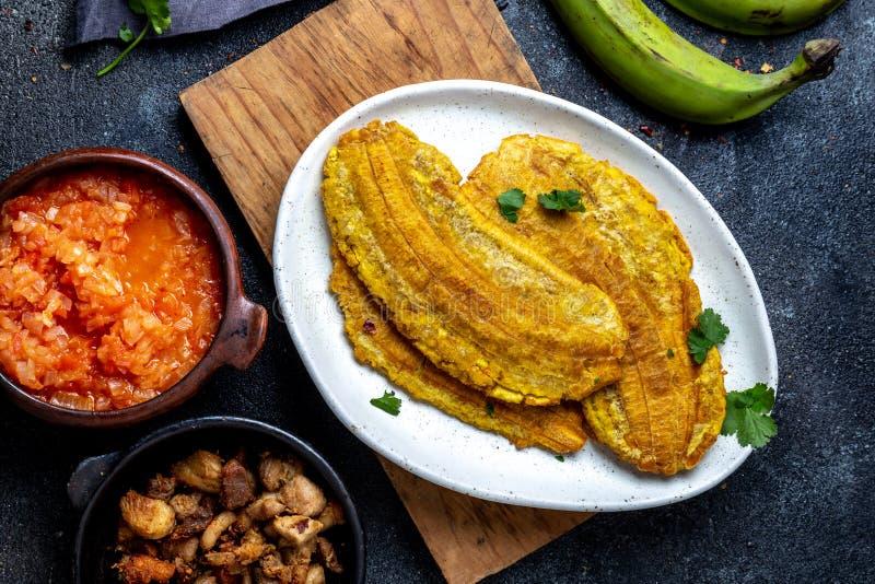 ΚΟΛΟΜΒΙΑΝΑ ΚΑΡΑΪΒΙΚΑ ΚΕΝΤΡΙΚΗΣ ΑΜΕΡΙΚΉΣ ΤΡΟΦΙΜΑ Patacon ή toston, τηγανισμένη και ισιωμένη ολόκληρη πράσινη plantain μπανάνα στο  στοκ φωτογραφία