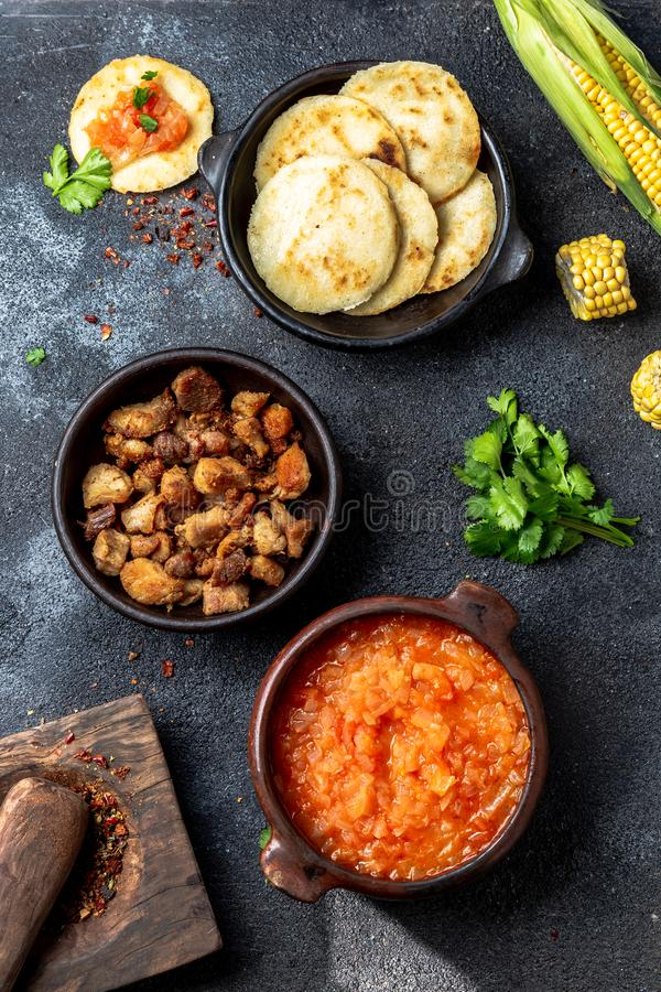 ΚΟΛΟΜΒΙΑΝΑ παραδοσιακά τρόφιμα Chicharron, arepas αραβόσιτου με την ντομάτα και τη σάλτσα κρεμμυδιών Τοπ όψη στοκ φωτογραφίες