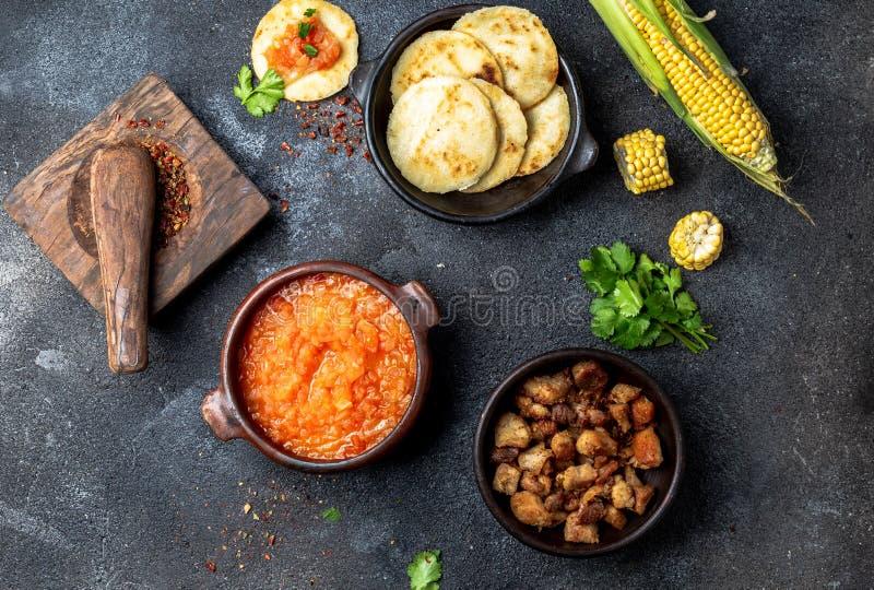 ΚΟΛΟΜΒΙΑΝΑ παραδοσιακά τρόφιμα Chicharron, arepas αραβόσιτου με την ντομάτα και τη σάλτσα κρεμμυδιών Τοπ όψη στοκ φωτογραφίες με δικαίωμα ελεύθερης χρήσης