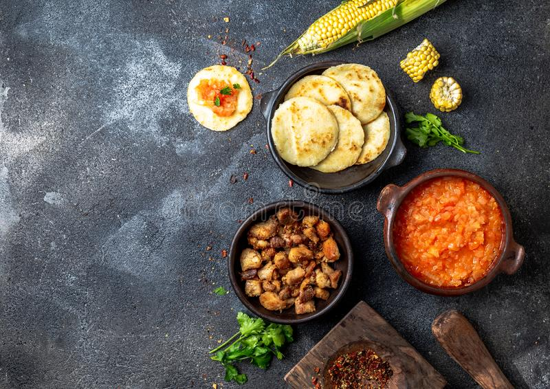 ΚΟΛΟΜΒΙΑΝΑ παραδοσιακά τρόφιμα Chicharron, arepas αραβόσιτου με την ντομάτα και τη σάλτσα κρεμμυδιών Τοπ όψη στοκ εικόνες