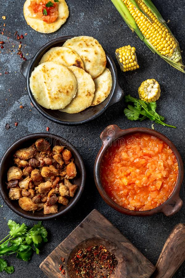 ΚΟΛΟΜΒΙΑΝΑ παραδοσιακά τρόφιμα Chicharron, arepas αραβόσιτου με την ντομάτα και τη σάλτσα κρεμμυδιών Τοπ όψη στοκ φωτογραφία