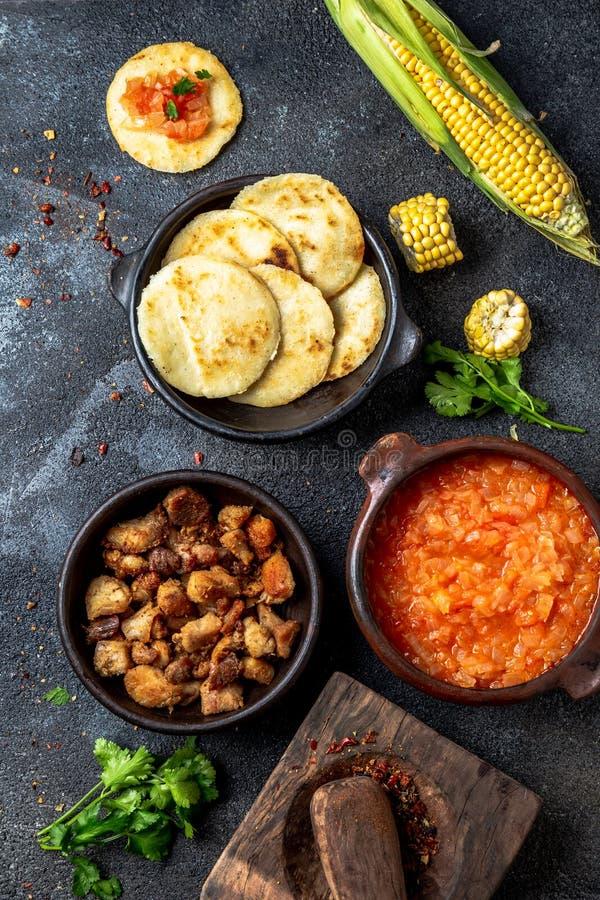 ΚΟΛΟΜΒΙΑΝΑ παραδοσιακά τρόφιμα Chicharron, arepas αραβόσιτου με την ντομάτα και τη σάλτσα κρεμμυδιών Τοπ όψη στοκ εικόνα