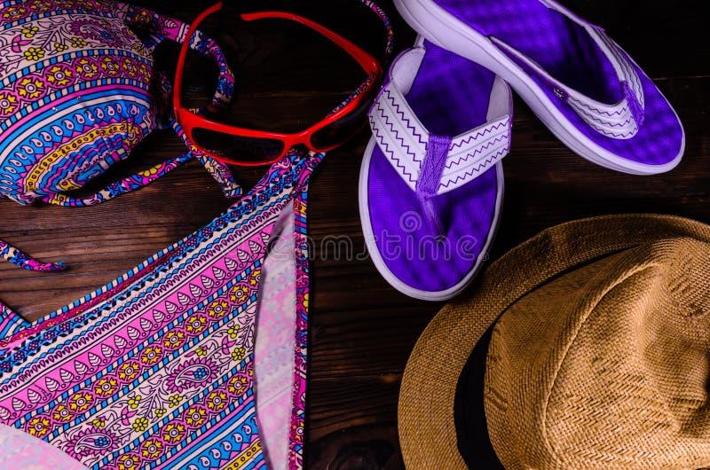 Κολυμπήστε το κοστούμι, το καπέλο, τα γυαλιά ηλίου και τις πτώσεις κτυπήματος σε έναν ξύλινο πίνακα κορυφή στοκ εικόνα με δικαίωμα ελεύθερης χρήσης