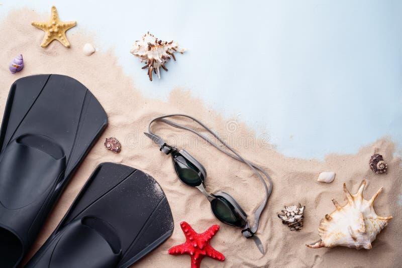 Κολυμπώντας προστατευτικά δίοπτρα και βατραχοπέδιλα στην άμμο με τα κοχύλια και τους αστερίες στοκ φωτογραφία